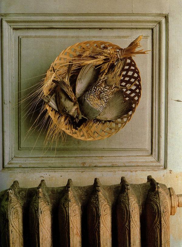 Birds in a basket hang above an engraved Victorian-era cast iron heat register