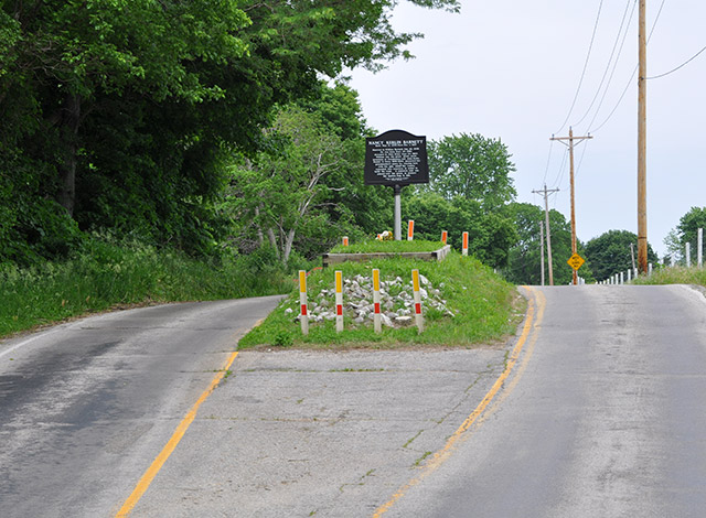 The grave of Nancy Kerlin Barnett rests in the middle of a road in rural Indiana