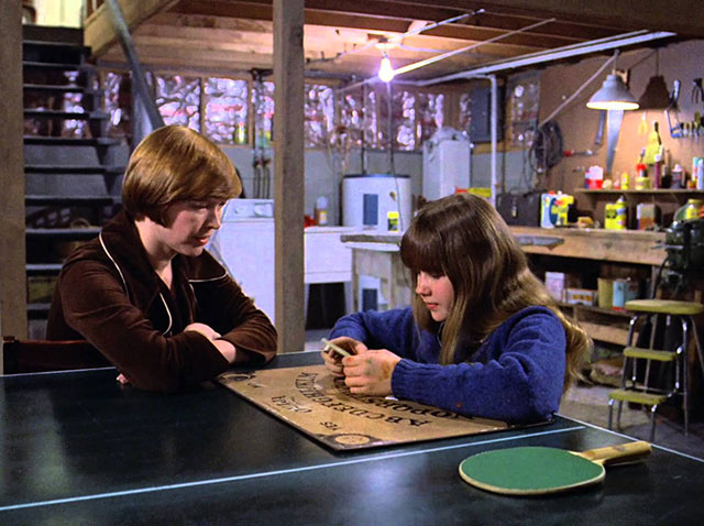 Regan plays with the Ouija board in The Exorcist