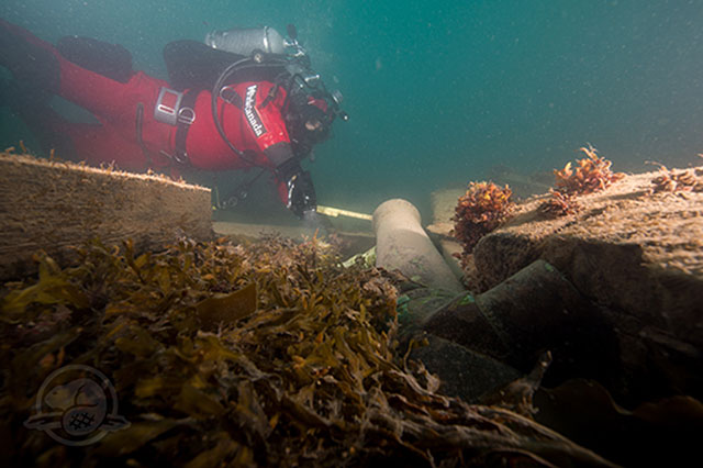 A diver examines a cannon in the wreck of the HMS Erebus